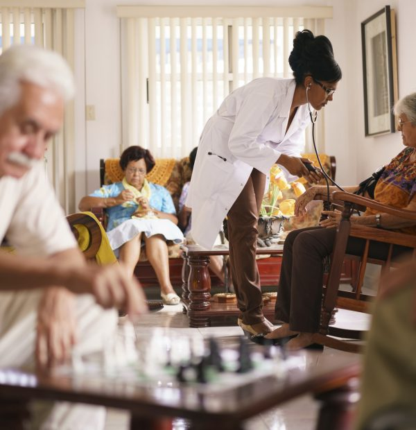 Old people in geriatric hospice: Black doctor visiting an aged patient, measuring blood pressure of a senior woman. Group of retired men in foreground playing chess.